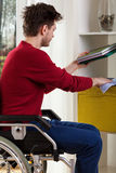 Man on wheelchair dusting shelves. Youmg man on wheelchair dusting shelves at home Royalty Free Stock Images