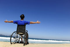 Man in wheelchair enjoying beach Stock Image