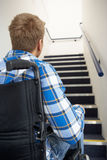 Man in wheelchair at foot of stairs Stock Image