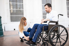 Man in wheelchair getting some help. Good looking young men in a wheelchair getting his legs in place with the help of his girlfriend stock image