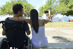 Man in wheelchair and girlfriend taking selfie. Disabled men in wheelchair and girlfriend in the park taking selfie royalty free stock photography