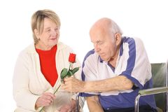 Man in wheelchair giving wife a rose stock images