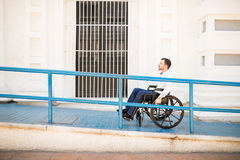 Man in wheelchair going up a ramp. Profile view of a good looking young man going up a building ramp on a wheelchair royalty free stock photography