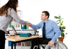 Man in wheelchair is greeting a woman Royalty Free Stock Photos