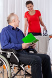 Man on wheelchair and helping nurse Stock Photos