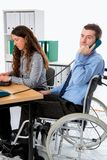 Man in wheelchair and his  is female colleague working in the jo Royalty Free Stock Images