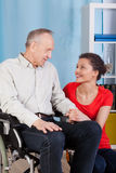 Man on wheelchair and his guardian Stock Photography