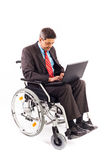 Man in a wheelchair with laptop Royalty Free Stock Images