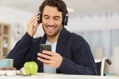 Man on wheelchair listening to music through headphone. Man on wheelchair listening to music through his headphone stock photo