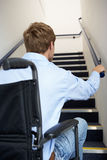 Man in wheelchair looking up at stairs. Man in wheelchair at bottom of stairs looking up holding handrail Stock Images