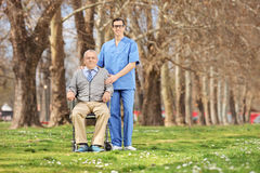 Man in a wheelchair and male nurse posing in park Royalty Free Stock Photos