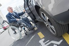 Man in wheelchair next to car Stock Photography