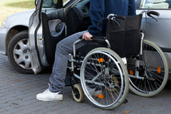 Man in wheelchair next to car Stock Photos