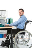 Man in wheelchair in the office Royalty Free Stock Photo