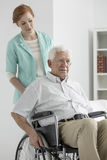 Man on a wheelchair. Older disabled men on a wheelchair and his helpful nurse royalty free stock photography