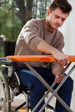 Man on wheelchair preparing iron board Stock Photos