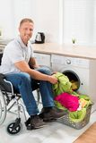 Man on wheelchair putting clothes into the washing machine Stock Photography