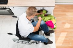 Man on wheelchair putting laundry into the washing machine Royalty Free Stock Image