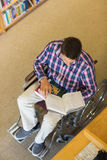 Man in wheelchair reading a book in library Royalty Free Stock Photos