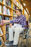 Man in wheelchair selecting book in library Stock Images