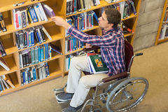 Man in wheelchair selecting book in the library Royalty Free Stock Image