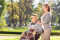 Man in wheelchair sitting with his wife in park Royalty Free Stock Photography