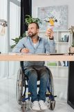 Man on wheelchair sitting at worktable. Thoughtful disabled man on wheelchair sitting at worktable with disposable cup of coffee stock images
