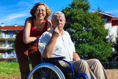 Man on wheelchair with smiling young woman. Man on wheelchair with optimistic young women in the park Stock Images
