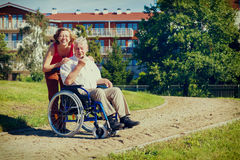 Man on wheelchair with smiling young woman. Man on wheelchair with optimistic young women in the park, vintage color Stock Image