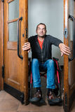 Man in wheelchair stuck between swing doors Royalty Free Stock Images