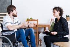 Man in wheelchair talking with psychotherapist stock photo