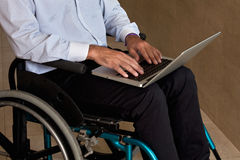 Man on Wheelchair Using Laptop Royalty Free Stock Images