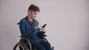 Man in wheelchair using modern cellular at home. Young and disabled man sitting in comfort wheel chair and spending free day at cozy house with modern and bright stock footage