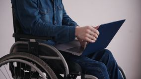 Man in wheelchair using modern personal computer at home. Adult disabled man sitting in special comfort wheelchair and spending his holiday at cozy house with stock video