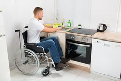 Man on wheelchair washing dishes Stock Images
