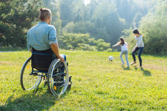 Man in a wheelchair watching his family play football Stock Photo