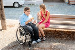 Man in wheelchair and woman eating nibbles spending time stock images