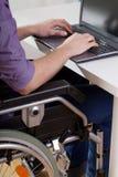 Man on wheelchair working on laptop Stock Photo