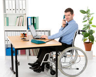 Man in wheelchair is working Stock Photography