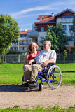 Man on wheelchair with young woman. Man on wheelchair with optimistic young women in the park Stock Images