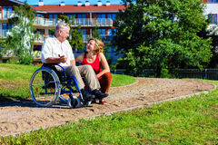 Man on wheelchair with young woman. Man on wheelchair with optimistic young women in the park Stock Photo