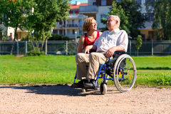 Man on wheelchair with young woman. Man on wheelchair with optimistic young women in the park Royalty Free Stock Photo