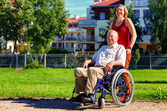 Man on wheelchair with young woman. Man on wheelchair with optimistic young women in the park with buildings in the background Royalty Free Stock Photos