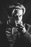 Man and whiskey. Man drinking whiskey alone in dark. Looking to camera. Black and white, male portrait stock image