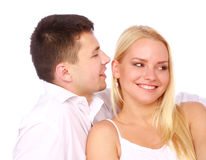 Man whisper a compliment. Happy couple in love on white background. Man whisper a compliment Royalty Free Stock Photo