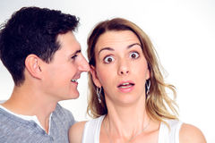 Man whisper in the ear of his girlfriend Stock Images