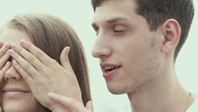 Man whispering in the ear of the girl. Tenderness. Couple in love. Boyfriend makes surprise his girlfriend. Girl with eyes closed. Man whispering in the ear of stock video footage