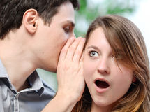 Man whispering in the ear of his surprised wife Royalty Free Stock Image