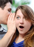 Man whispering in the ear of his surprised wife Stock Photography