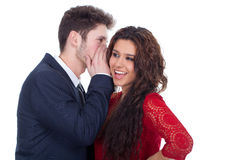 Man whispering a secret to a surprised lady Stock Images